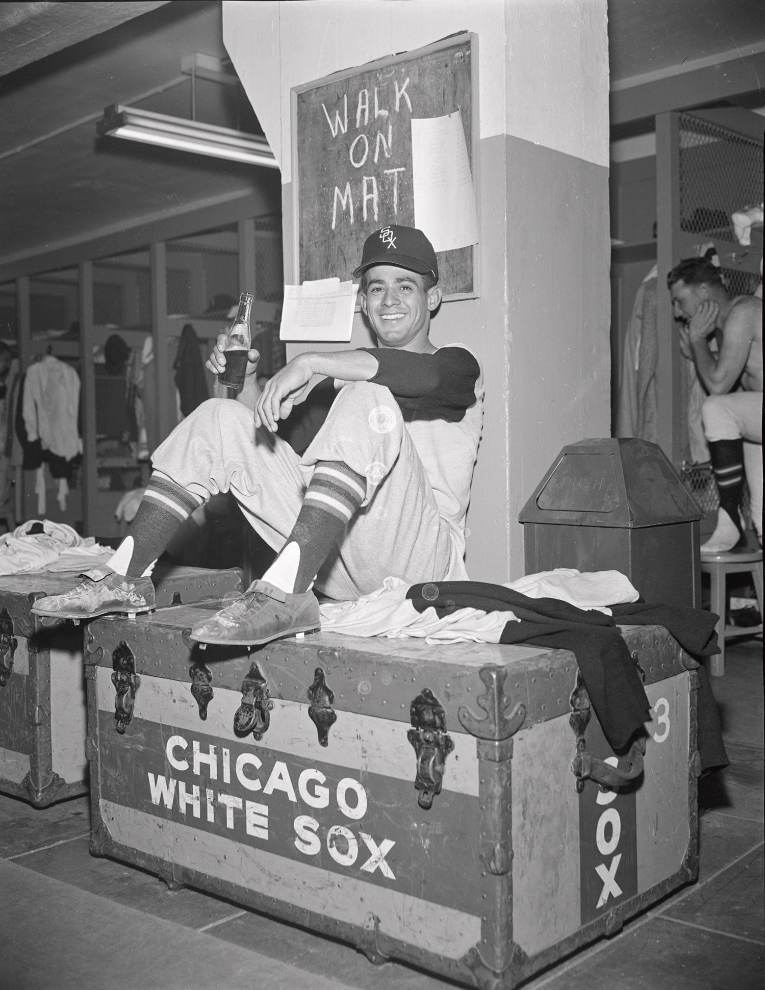 """A black-and-white negative of Luis Aparicio sitting on a travel trunk in the visitor's clubhouse at Yankee Stadium in the late 1950s. <a href=""""https://collection.baseballhall.org/islandora/object/islandora%3A629589"""">PASTIME</a> (Osvaldo Salas/National Baseball Hall of Fame and Museum)"""