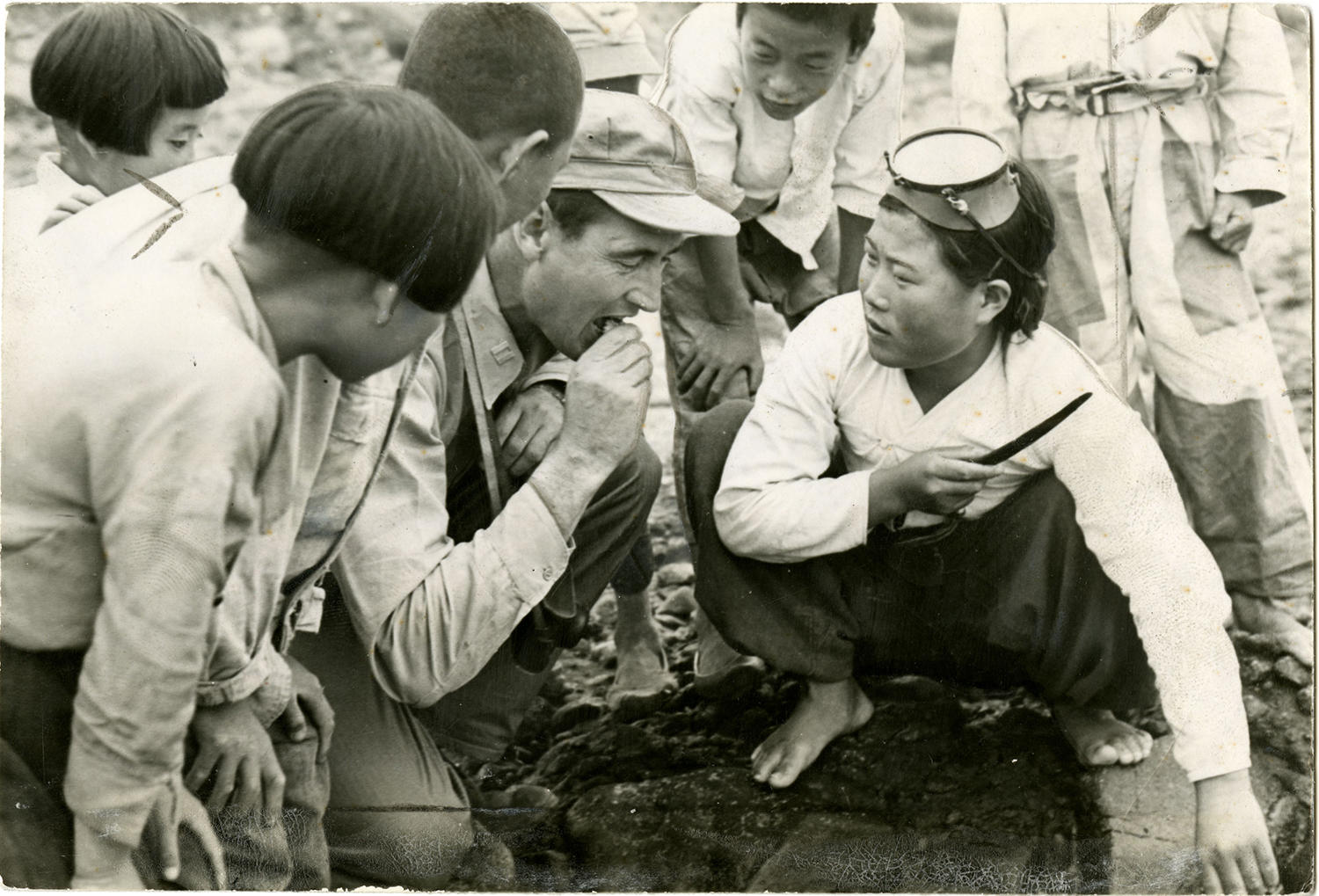 """While exploring a Korean village, Williams stopped to eat a live clam, offered by a local diving woman. Children watch his reaction as he eats. <a href=""""http://collection.baseballhall.org/islandora/object/islandora%3A501831"""">PASTIME</a> (National Baseball Hall of Fame)"""
