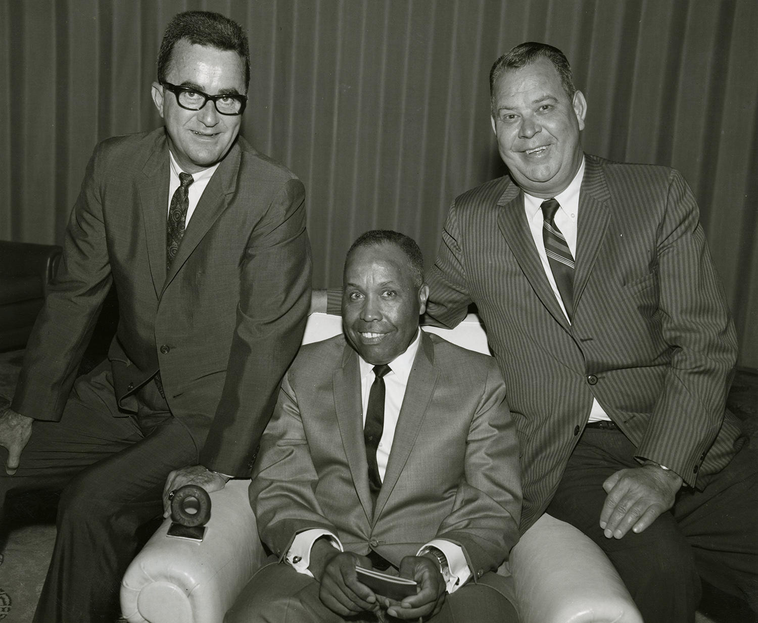 "Emmett Ashford (center) poses with executives Howard Fox (left) and Calvin Griffith. <a href=""http://collection.baseballhall.org/islandora/object/islandora%3A397295"">PASTIME</a> (National Baseball Hall of Fame and Museum)"