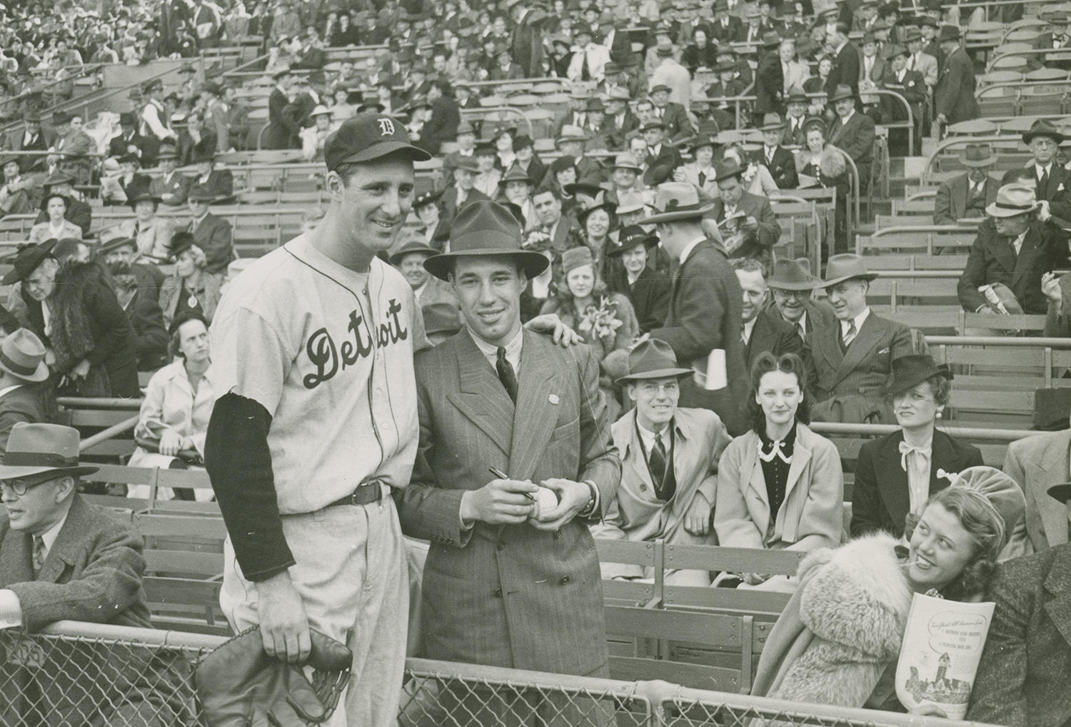 "Bob Feller poses for a photograph with Detroit Tigers' star Hank Greenberg. Feller, standing on the spectator side of the fence, is seen holding a baseball and marker, waiting for an autograph. <a href=""https://collection.baseballhall.org/islandora/object/islandora%3A612130"">PASTIME</a> (National Baseball Hall of Fame and Museum)"