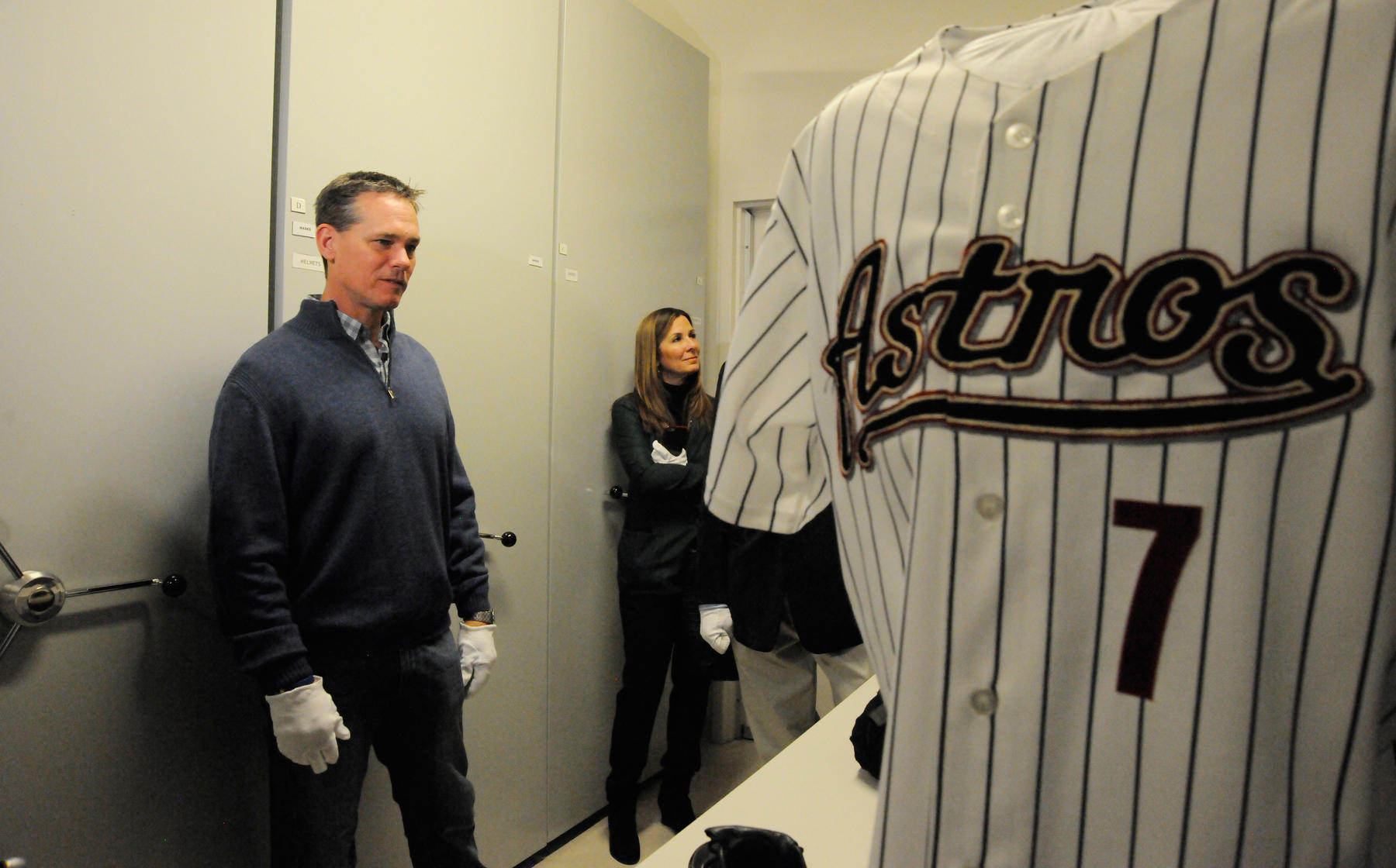 Craig Biggio and his wife Patty check out some of his artifacts in the Hall of Fame collection, including an Astros jersey he wore on Opening Day 2003 with a patch (not seen) honoring the Space Shuttle Columbia astronauts who died on Feb. 2, 2003. (Milo Stewart Jr. / National Baseball Hall of Fame)