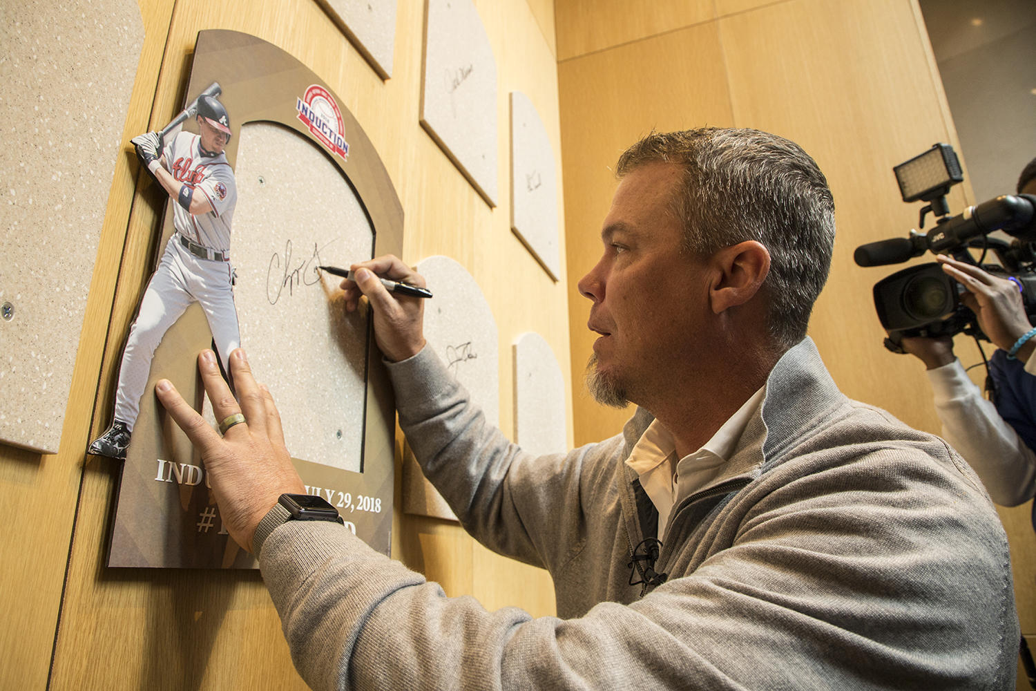 Chipper Jones signs the backer where his bronze plaque will be placed following his Hall of Fame induction on July 29. (Milo Stewart Jr./National Baseball Hall of Fame and Museum)