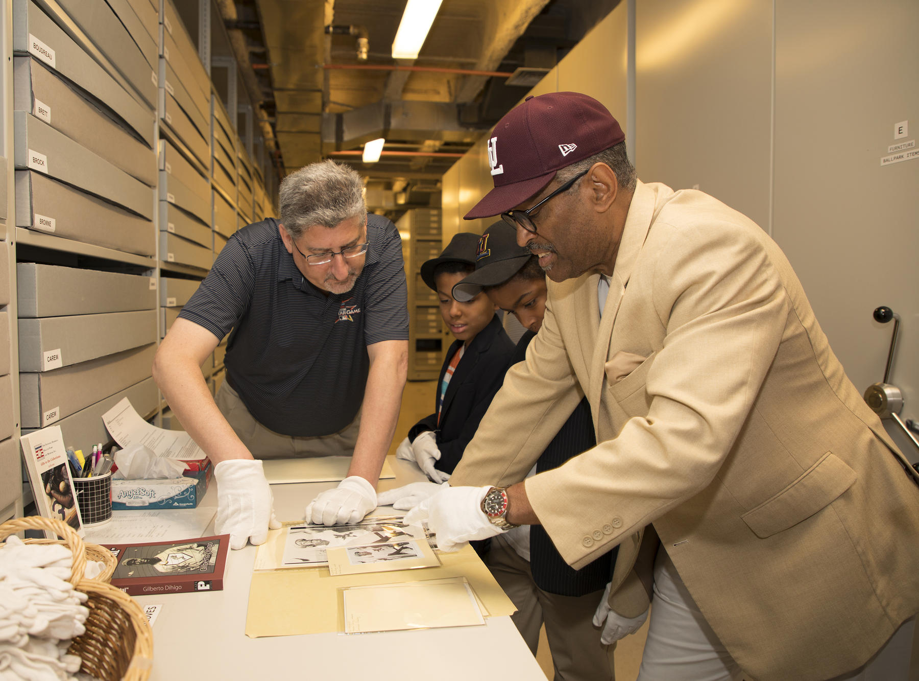 Hall of Fame vice president for exhibitions and collections Erik Strohl shows Gilberto Dihigo, son of Hall of Famer Martin Dihigo, artifacts from the Museum's collection. Gilberto's sons Gilbert and Gregory look on as well. (Milo Stewart Jr./National Baseball Hall of Fame and Museum)