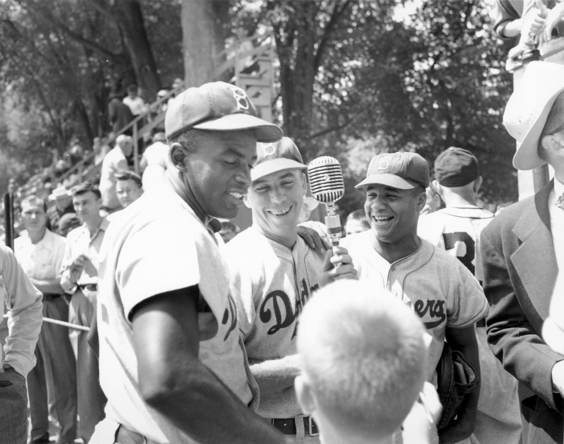 A trio of future Hall of Famers - the Brooklyn Dodgers's Jackie Robinson, Pee Wee Reese and Roy Campanella - surround a microphone at the 1951 Hall of Fame Game in Cooperstown. BL-595.2005.9 (Nationals Baseball Hall of Fame Library)