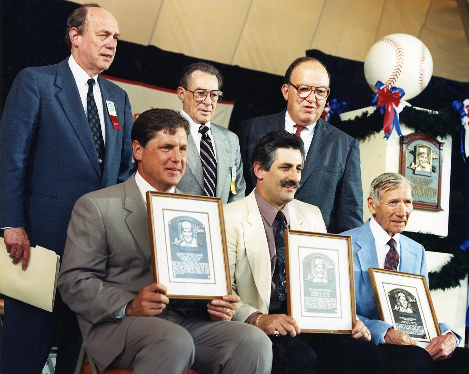 (Bottom row, from left to right): Tom Seaver, Rollie Fingers and Hal Newhouser pose with images of their bronze plaques following the 1992 <em>Induction Ceremony</em>. In the top row, (from left to right) are Chairman of the Board Ed Stack, Bill McGowan Jr. and Commissioner Fay Vincent. (Milo Stewart Jr. / National Baseball Hall of Fame and Museum)