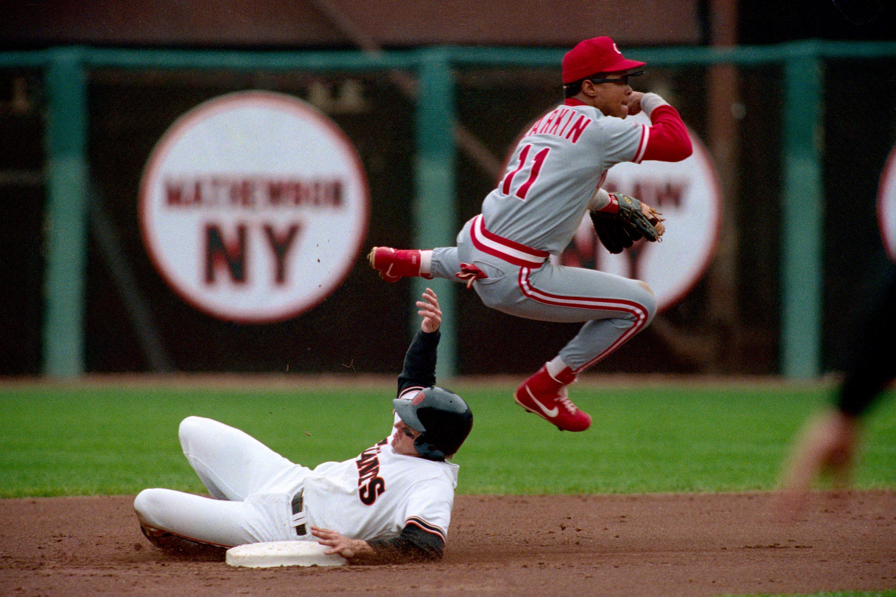 Cincinnati Reds shortstop Barry Larkin turns a double play at second base in a game against the San Francisco Giants in 1990. Larkin earned three consecutive Gold Glove Awards with the Reds from 1994-96. (Brad Mangin / National Baseball Hall of Fame Library)