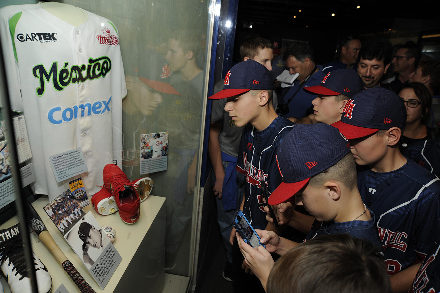 """Maine-Endwell Little Leaguers check out their own artifacts on display in the Museum's """"Whole New Ballgame"""" exhibit, which include a team-signed baseball, a team photo and a championship ticket. (Milo Stewart Jr. / National Baseball Hall of Fame)"""