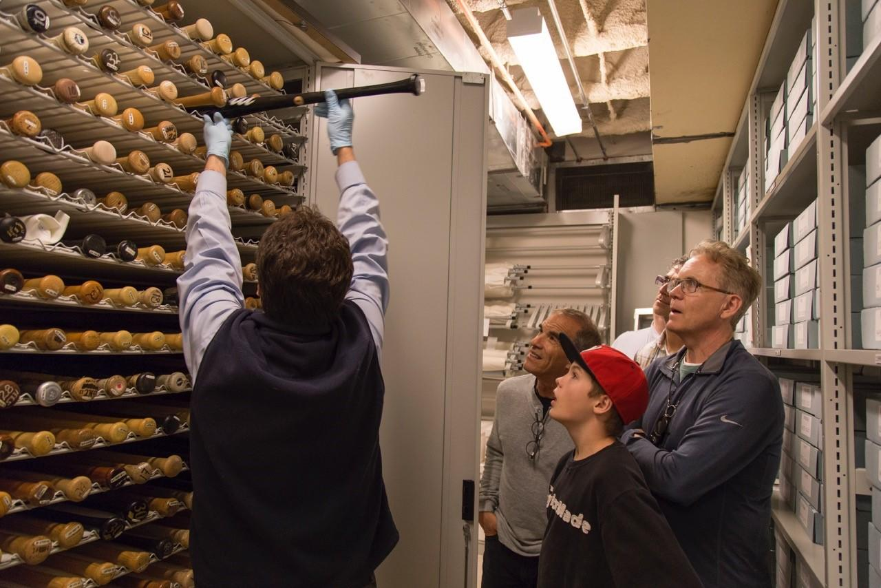Mark Frost, who helped create the TV show Twin Peaks, watches with his son, Travis, and Frost's lawyer, Alan S. Wertheimer, as Hall of Fame Senior Curator Tom Shieber takes a bat out of the Museum's collection during a tour. (Parker Fish / National Baseball Hall of Fame)