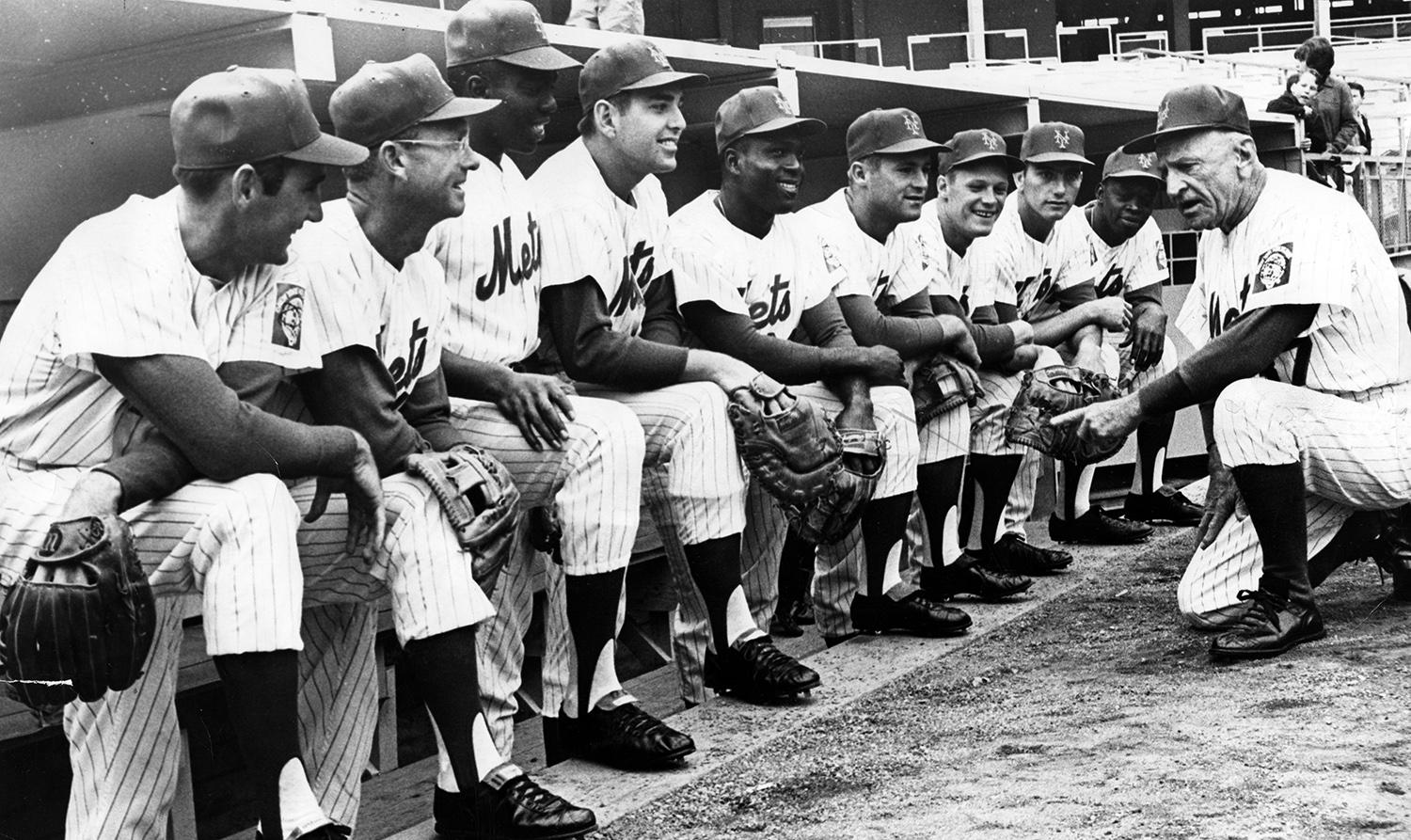 Casey Stengel talks to his Opening Day lineup on April 12, 1965. From left to right:  Billy Cowan, Roy McMillan, Johnny Lewis, Ed Kranepool, Joe Christopher, Charley Smith, Billy Klaus, Chris Cannizzaro and Al Jackson. (National Baseball Hall of Fame)