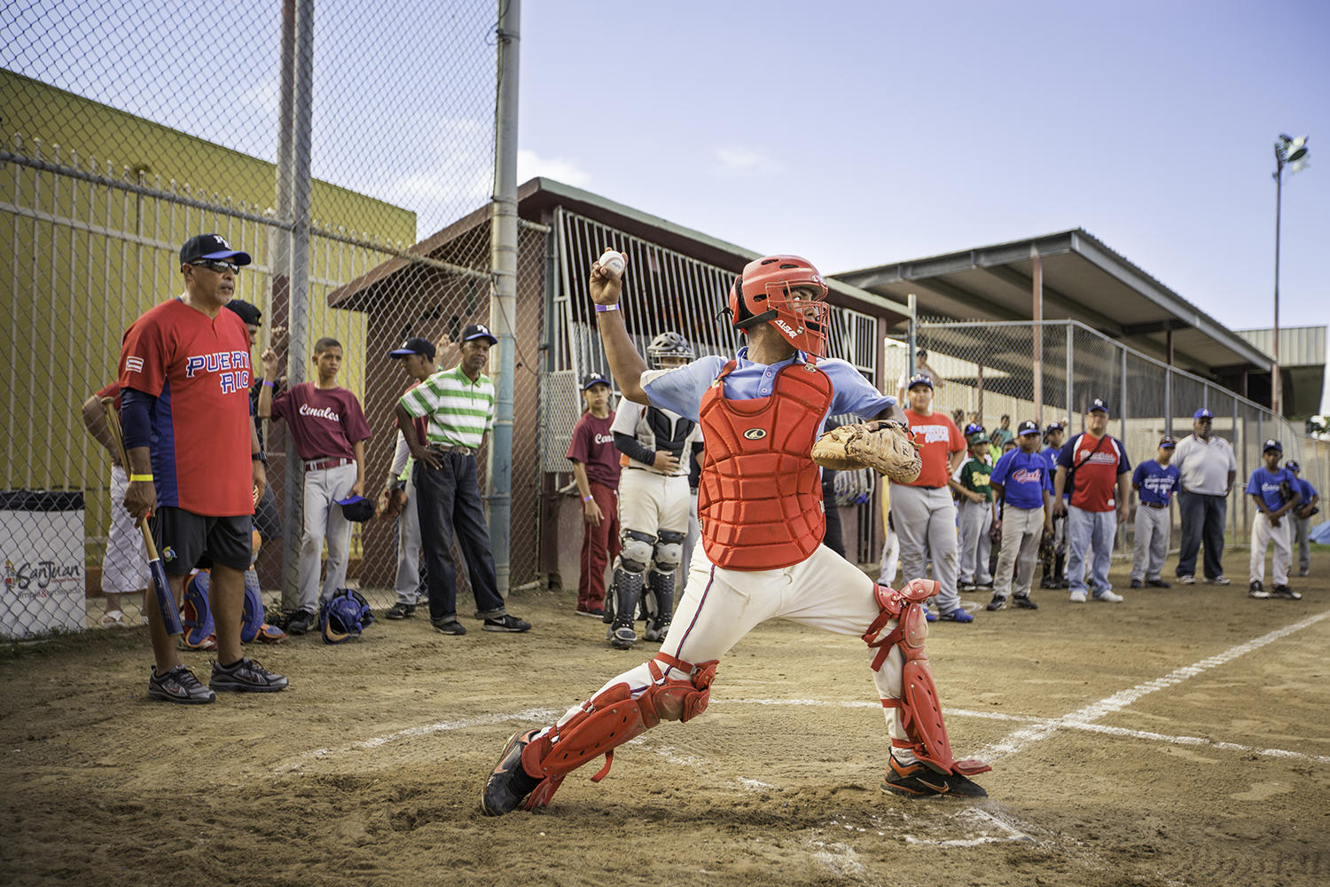 Former player Edwin Rodríguez (far left) works with a catcher during a baseball clinic for kids at the Canales low income housing project in San Juan, Puerto Rico on December 27, 2014. The stories of baseball players throughout Latin America will be told on La Vida Baseball's platform. (Jean Fruth / National Baseball Hall of Fame)