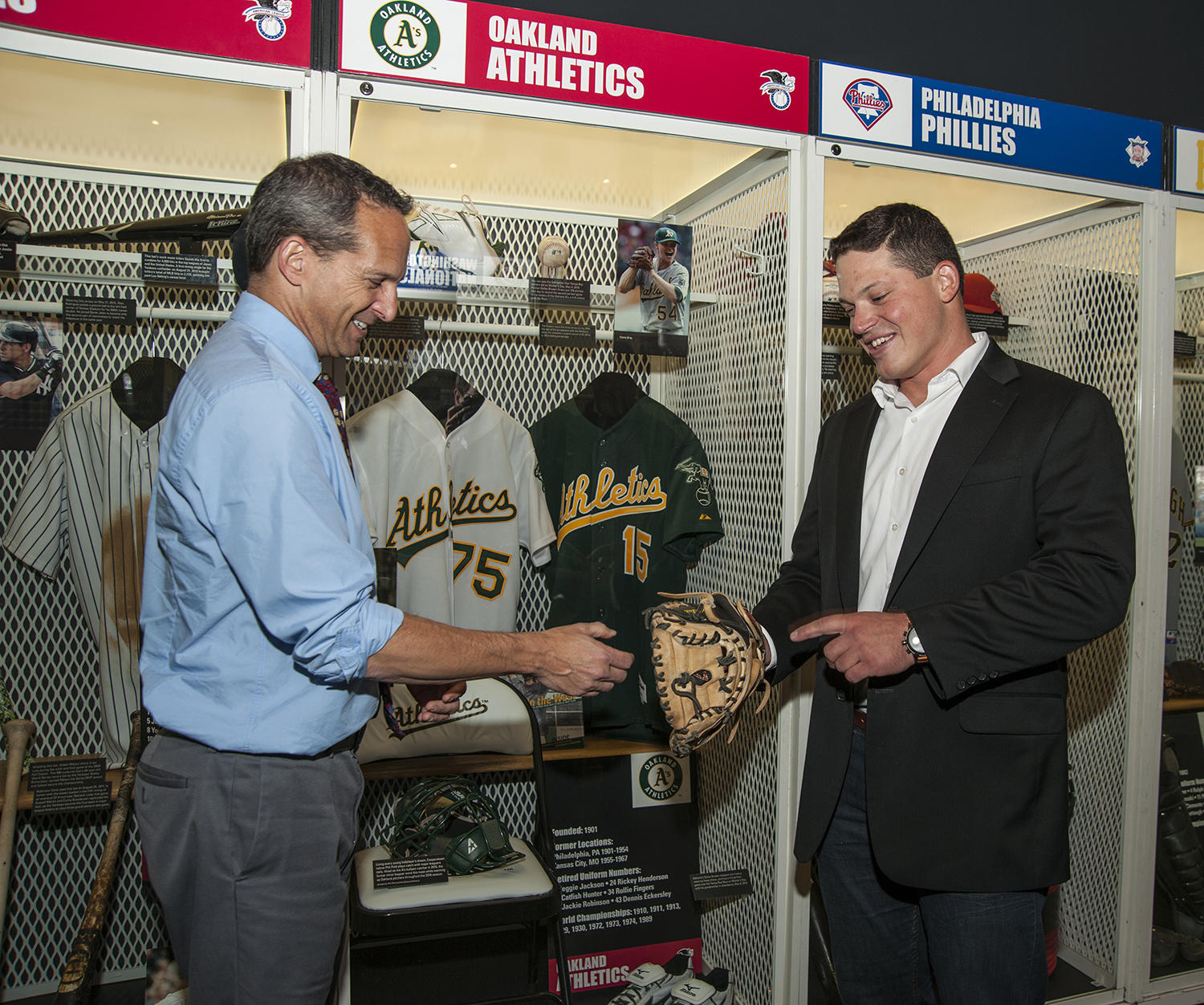 Phil Pohl shows off his glove to Hall of Fame President Jeff Idelson, outside of the A's locker on the second floor of the Museum. (Milo Stewart Jr. / National Baseball Hall of Fame)
