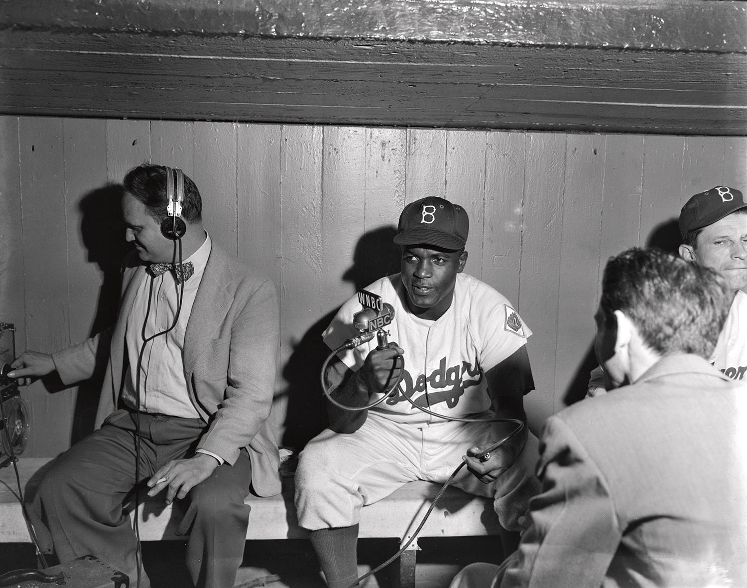 """A black-and-white negative of Jackie Robinson holding a microphone in the home dugout of Ebbets Field, taken in 1951. <a href=""""https://collection.baseballhall.org/islandora/object/islandora:627941"""">PASTIME</a> (Osvaldo Salas/National Baseball Hall of Fame and Museum)"""