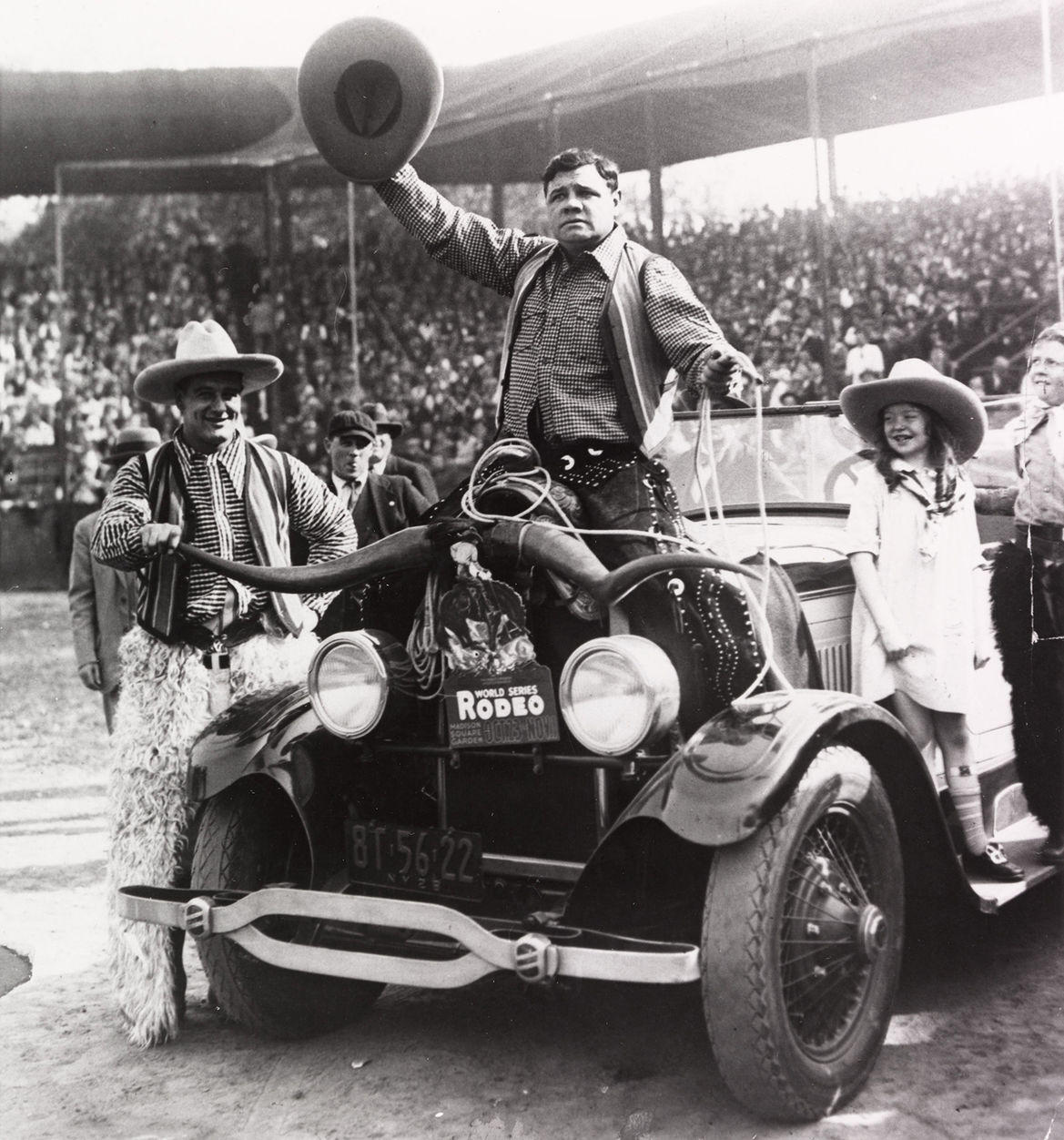 """Babe Ruth sits on a car and waves his cowboy hat to the crowd while Lou Gehrig stands beside the car and smiles during an advertising stunt for the World Series Rodeo. <a href=""""http://collection.baseballhall.org/islandora/object/islandora%3A214527"""">PASTIME</a>"""