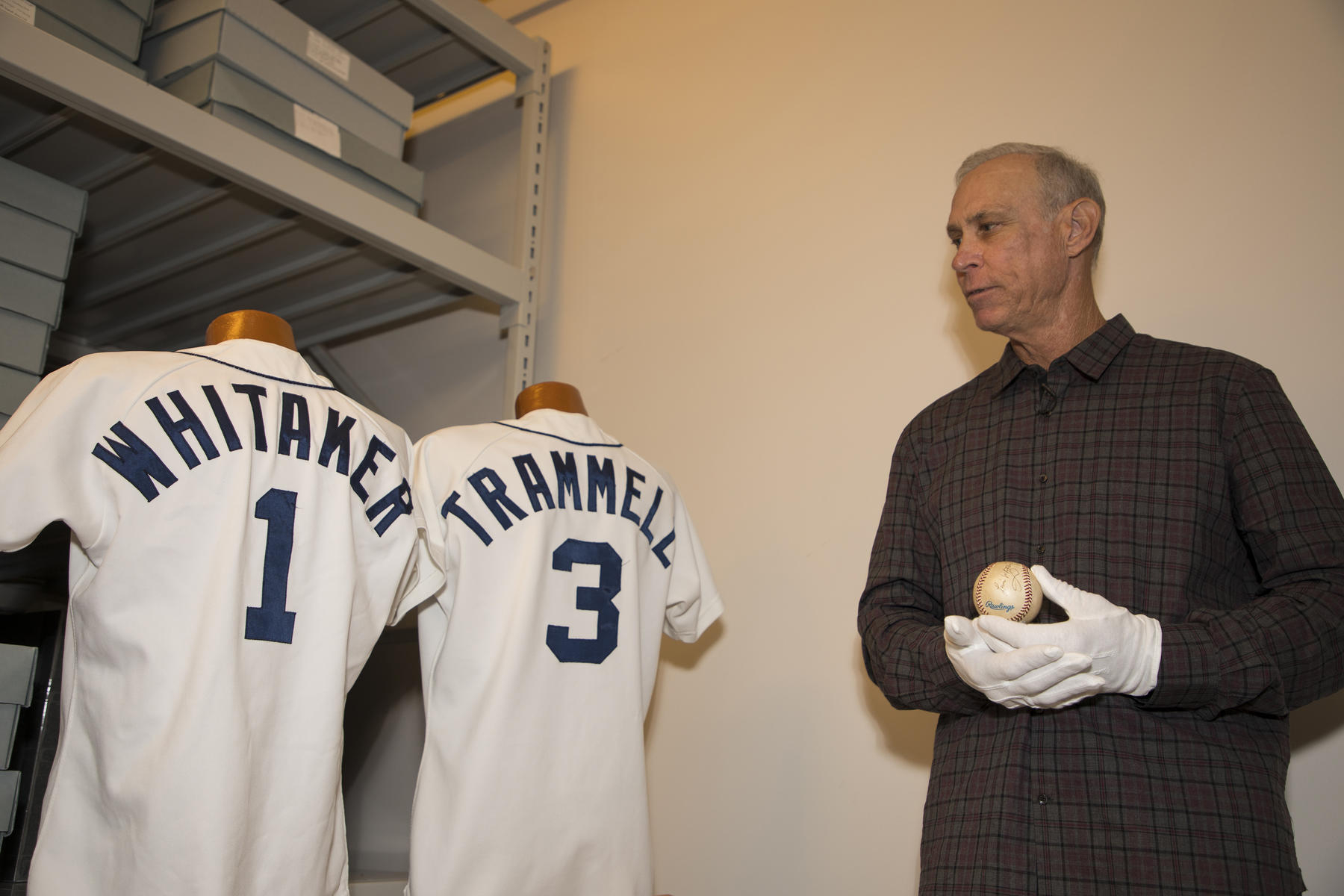 During his Orientation Visit to the Hall of Fame on March 15, Class of 2018 member Alan Trammell holds a baseball used in 1995 when he and Lou Whitaker set an American League record for most games as teammates. In the background are jerseys worn by Whitaker (in 1984) and Trammell (in 1983) which are a part of the Museum's collection. (Milo Stewart Jr./National Baseball Hall of Fame and Museum)