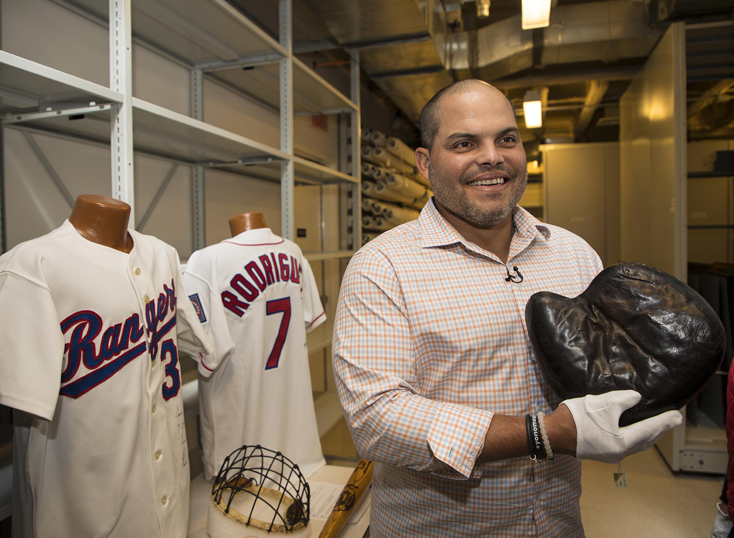 Iván Rodríguez poses with Joe Gunson's original catchers' mitt during his Orientation Tour of the Hall of Fame.  Gunson, was one of the earliest adopters of the catcher's mitt.  (Milo Stewart Jr. / National Baseball Hall of Fame)