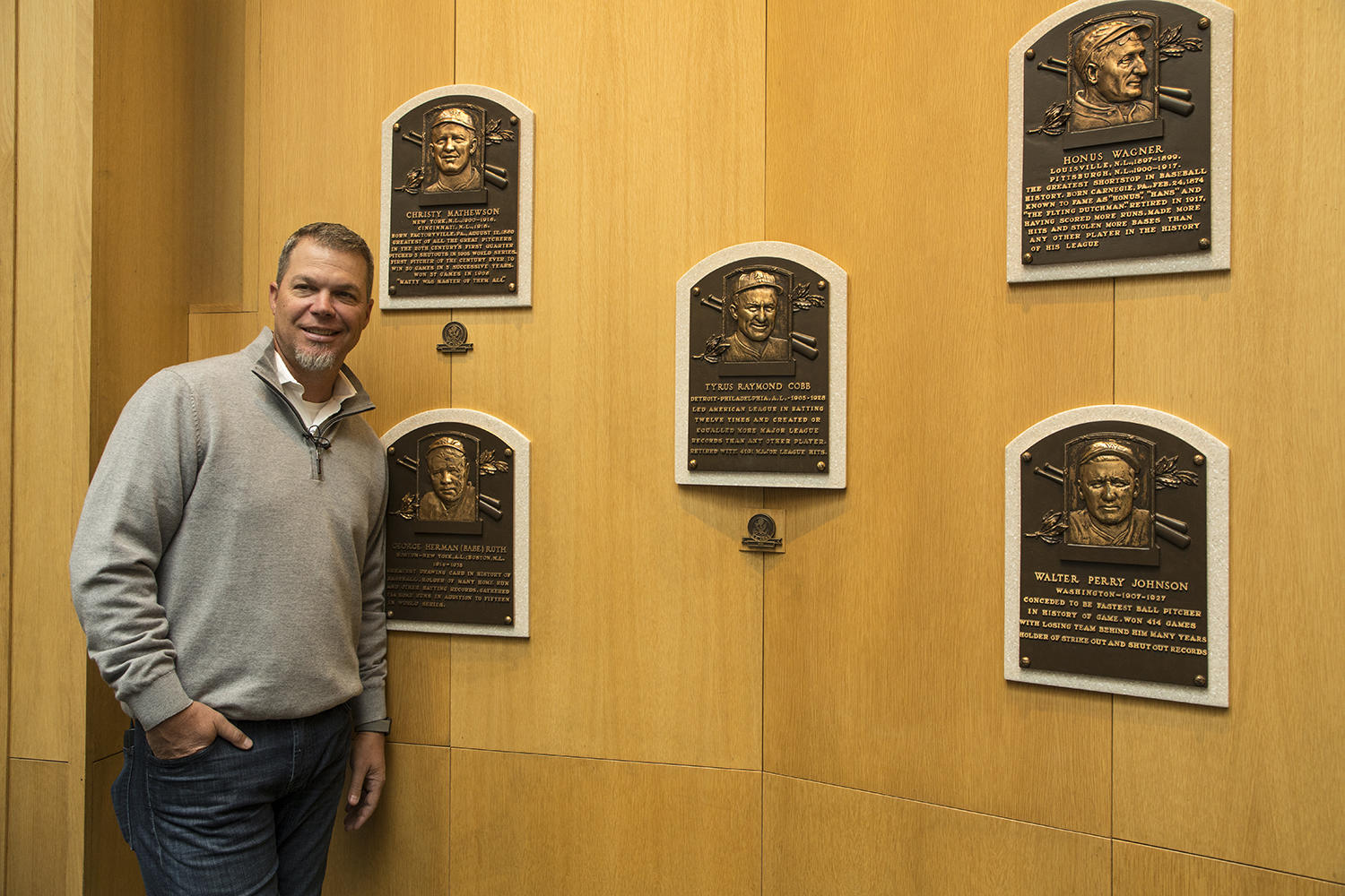 Chipper Jones poses with the bronze plaques representing the Hall of Fame's Class of 1936 during his trip to Cooperstown. (Milo Stewart Jr./National Baseball Hall of Fame and Museum)