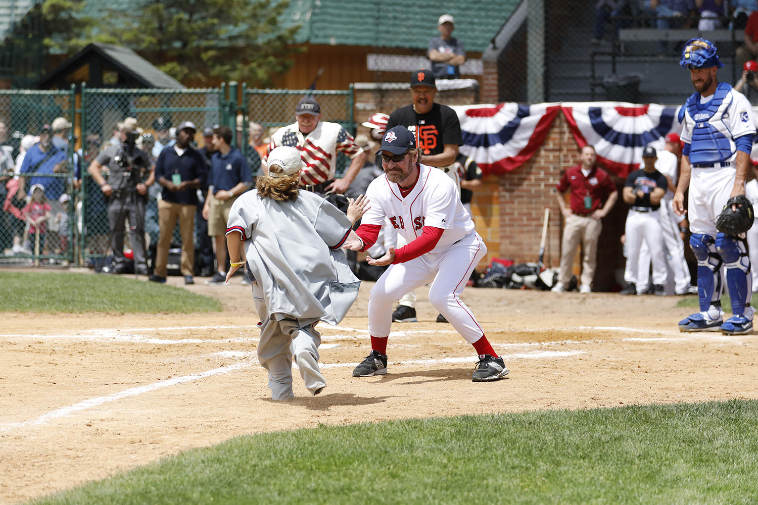 Hall of Famer Wade Boggs welcomes home a runner during a between-innings contest at the Hall of Fame Classic. (Milo Stewart Jr./National Baseball Hall of Fame and Museum)