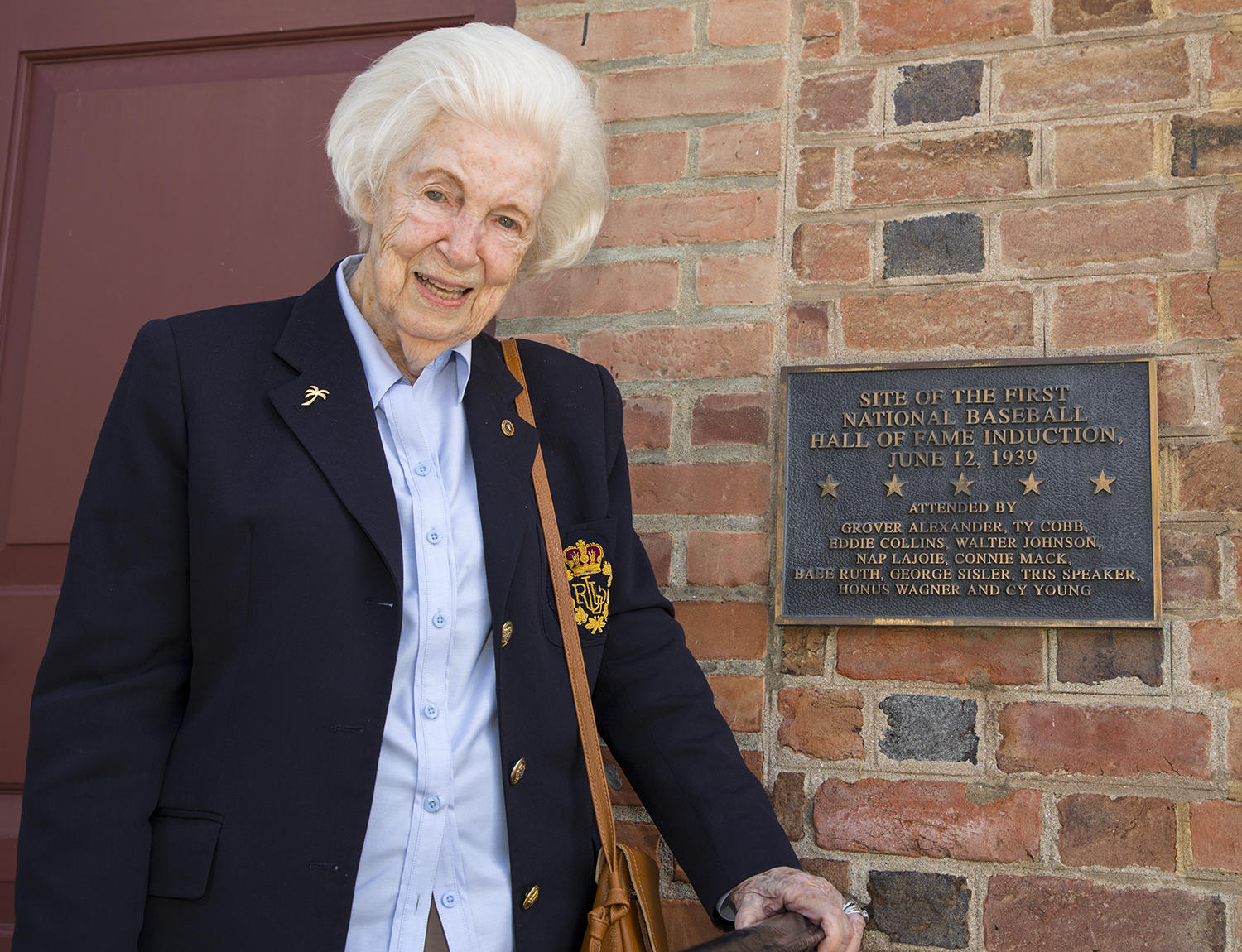Betty Roxborough poses next to a plaque commemorating the first Hall of Fame Induction on June 12, 1939. (Milo Stewart Jr. / National Baseball Hall of Fame and Museum)