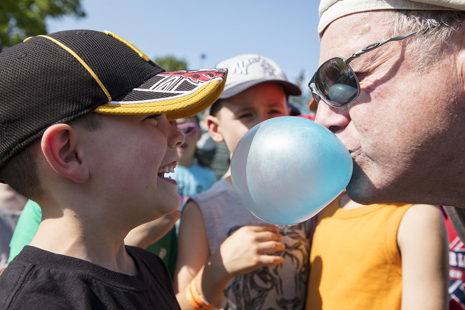 The inventor of Big League Chew, Rob Nelson, shows a young fan how to properly blow a bubble. (Milo Stewart Jr./National Baseball Hall of Fame and Museum)