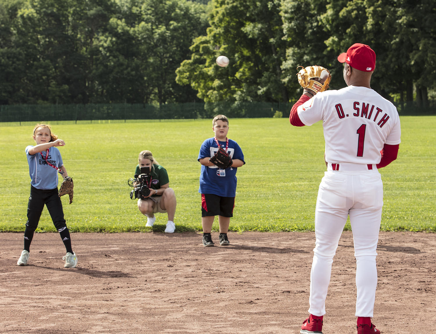 Ozzie Smith plays catch with a young fan on Friday in Cooperstown during the PLAY Ball event. (Milo Stewart Jr./National Baseball Hall of Fame and Museum)