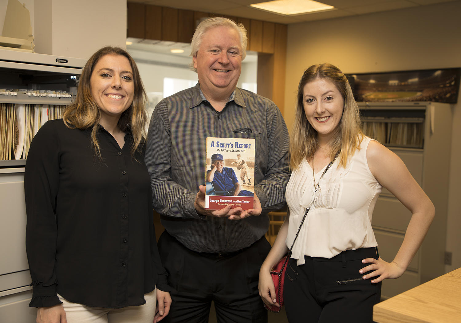 """George Genovese's granddaughters Rose Hayworth (left) and Holly Hayworth (right) pose with Dan Taylor, who co-wrote Genovese's memoir, """"A Scout's Report: My 70 Years in Baseball."""" (Milo Stewart Jr./National Baseball Hall of Fame and Museum)"""
