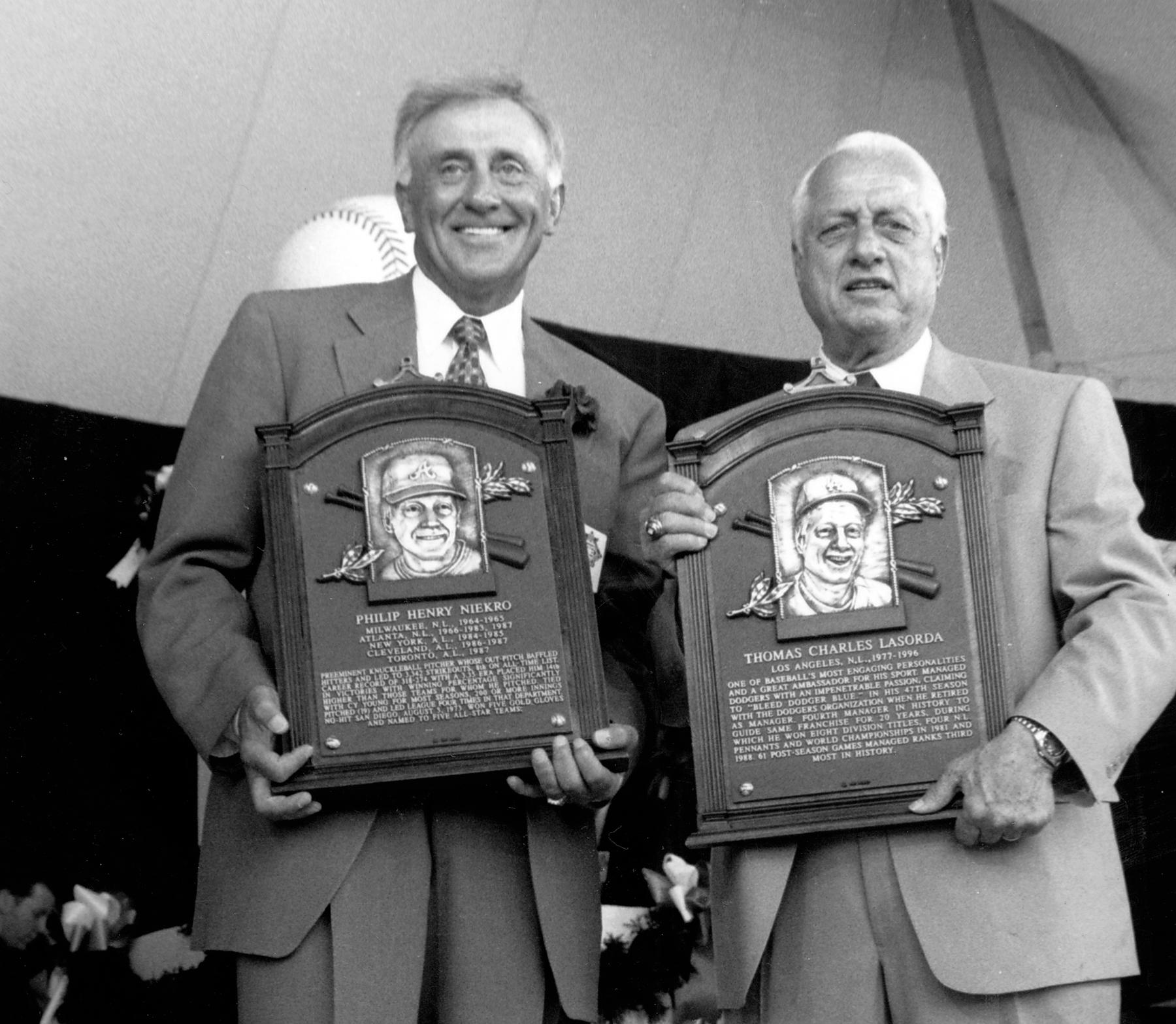 A detail view of Phil Niekro, left, and Tommy Lasorda holding their plaques on stage at the 1997 Hall of Fame Induction Ceremony. BL-17.99 (National Baseball Hall of Fame Library)