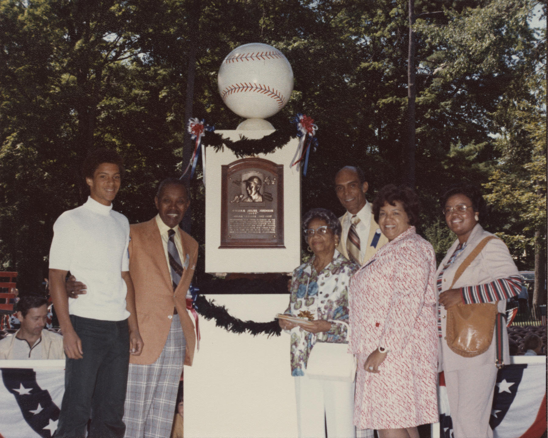 Judy Johnson standing in front of his plaque with family members. BL-549.2012.25 (National Baseball Hall of Fame Library)