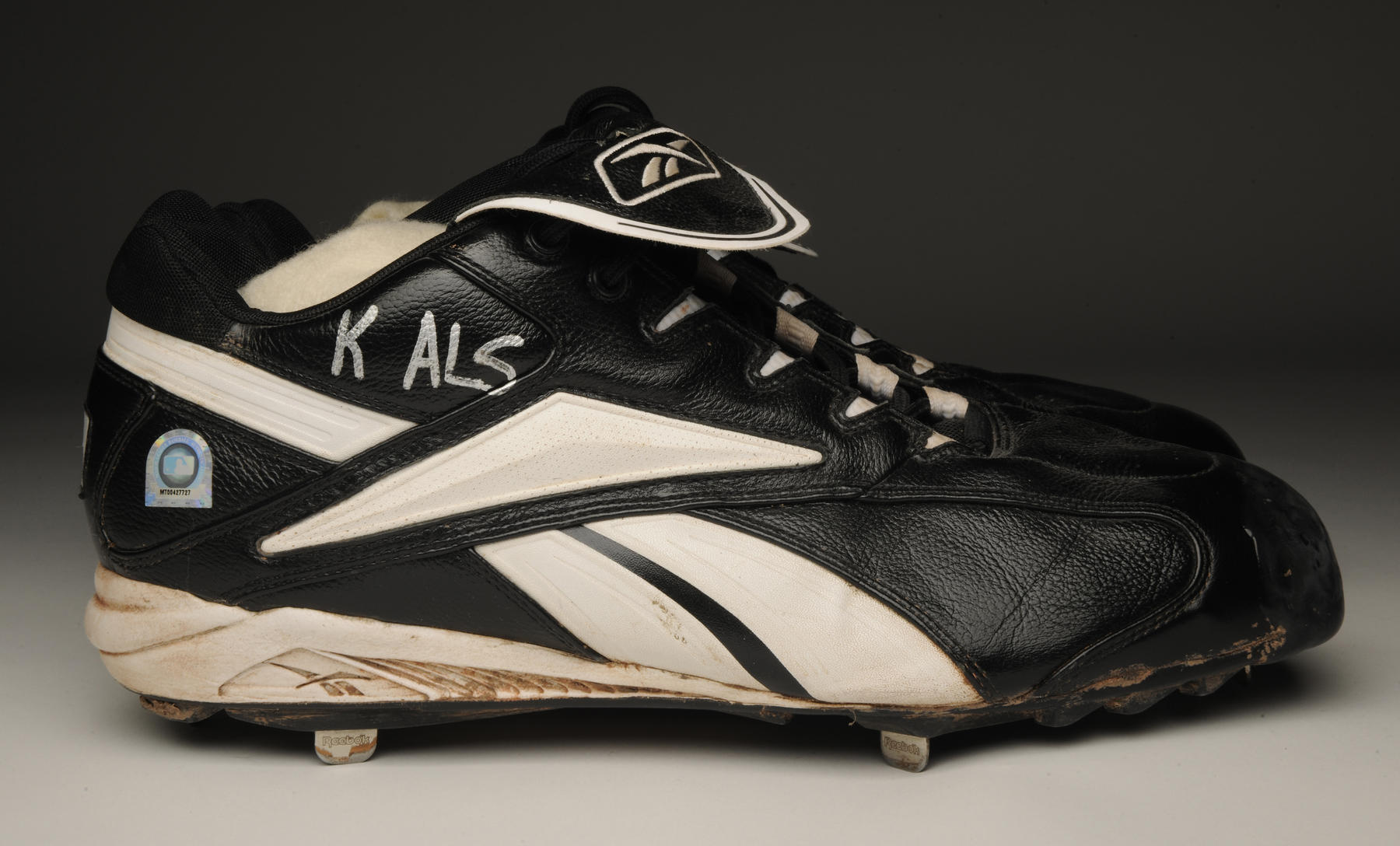 """Curt Schilling's right cleat worn during the 2004 World Series with """"K ALS"""" written in silver marker. B-337.2004 (Milo Stewart Jr. / National Baseball Hall of Fame and Museum)"""