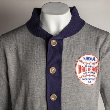 This exclusive cardigan sweater is crafted with 450 gram weight 100% acrylic, knit in quarry gray with the shawl collar, placket, hem, and cuffs knit in patriot blue.