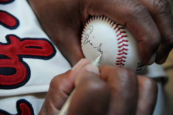 Hall of Famer Ozzie Smith signs a baseball during the 14th annual PLAY Ball fundraiser Friday at the Clark Sports Center in Cooperstown. (Milo Stewart, Jr. / National Baseball Hall of Fame)