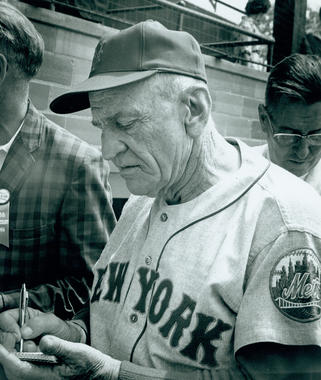 Future Hall of Famer Casey Stengel signs an autograph at the Hall of Fame Game on July 27, 1964.  He would be inducted into the Hall of Fame two years later. (National Baseball Hall of Fame and Museum)