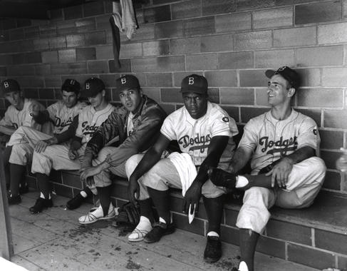 Six Brooklyn Dodgers sitting in the dugout at Doubleday.  From left to right: Phil Haugstad, Preacher Roe, Clem Labine, Don Newcombe, Jackie Robinson and Cal Abrams. (National Baseball Hall of Fame and Museum)