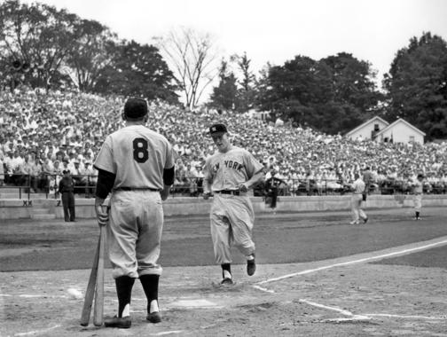 Mickey Mantle crosses home plate, scoring another run for the Yankees. Yogi Berra is standing in the foreground with his back to the camera. BL-1306.2002 (National Baseball Hall of Fame)