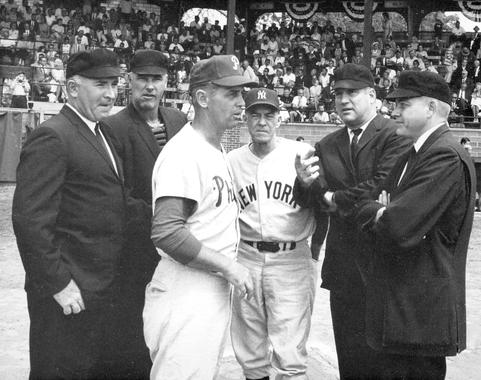 Johnny Keane, manager of the New York Yankees, and Gene Mauch, the manager of the Philadelphia Phillies, meet with the umpires. (Wyer)