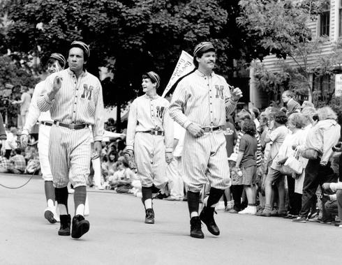 Participants don Mudville jerseys walk down the street for the 50th Anniversary Hall of Fame Parade. Along with the Hall of Fame Game, the Parade was among many events that took place during Hall of Fame Weekend in 1989.(National Baseball Hall of Fame and Museum)