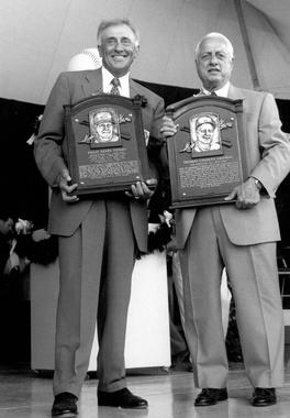 Hall of Famers Phil Niekro (left) and Tommy Lasorda stand with their plaques after being inducted to the National Baseball Hall of Fame and Museum in 1997. BL-17-99 (National Baseball Hall of Fame Library)