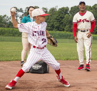 Ozzie Smith helps a young fan with his fielding form during PLAY Ball on Friday in Cooperstown. The Museum fundraiser hosted by Smith, the Hall of Fame's Education Ambassador, raised nearly $40,000 for the Museum's education mission this year. (Parker Fish/National Baseball Hall of Fame and Museum)