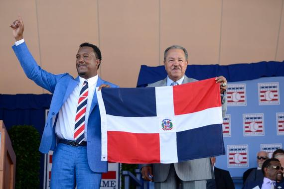 Class of 2015 Hall of Fame inductee Pedro Martínez holds the flag of the Dominican Republic with Juan Marichal (Class of 1983) at the Induction Ceremony on Sunday in Cooperstown. Marichal received a standing ovation from the fervent Dominican fans in attendance when he was introduced onto the stage. (Milo Stewart, Jr. / National Baseball Hall of Fame)