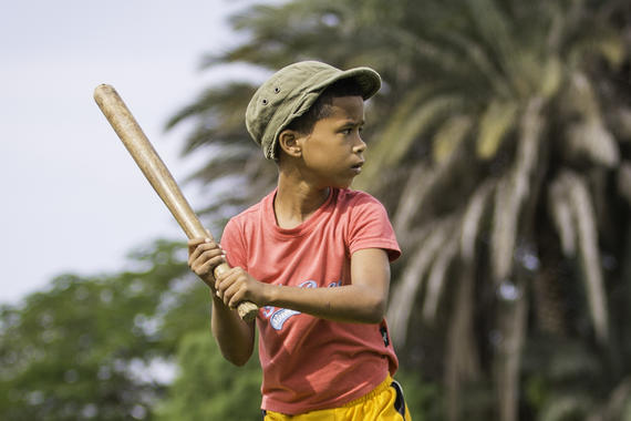 A young kid plays baseball in a park on the outskirts of Havana on January 11, 2015 in Havana, Cuba. (Jean Fruth / National Baseball Hall of Fame)