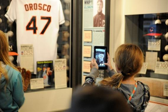 A young visitor using an iPad to take a photo of a Jesse Orosco uniform displayed in the Museum. (Milo Stewart Jr. / National Baseball Hall of Fame)