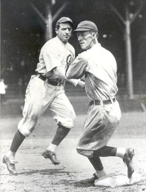 Johnny Evers, in the foreground, tagging a base and preparing to throw the ball. Joe Tinker can be seen in the background. BL-636.78