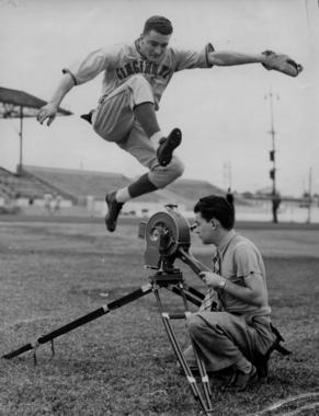 Reds first baseman Frank McCormick leaps over a camera set up on the field. BL-6552.70 (National Baseball Hall of Fame Library)