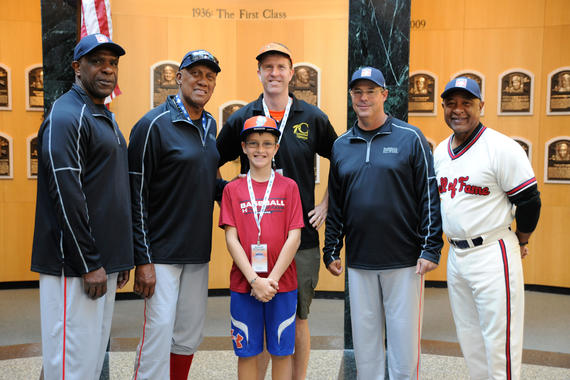 Erik Nielsen of Houston and his son, Sam, share a moment with Hall of Famers (from left) Andre Dawson, Fergie Jenkins, Greg Maddux and Ozzie Smith during the 2015 PLAY Ball event in Cooperstown. PLAY Ball participants have the chance to meet Hall of Famers in the Museum's Plaque Gallery before heading to the diamond for on-field instruction and interaction. (Milo Stewart Jr./National Baseball Hall of Fame)