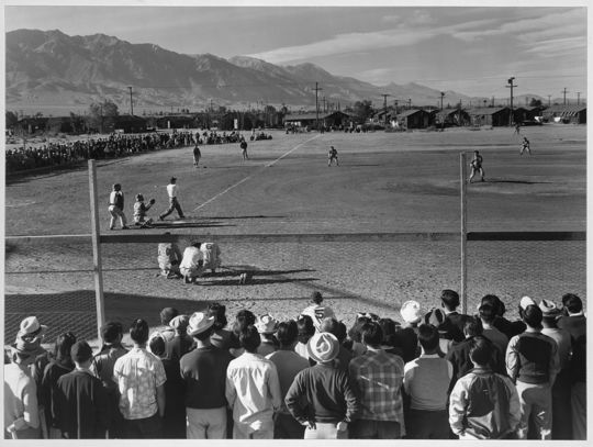 Internees pack the stands to watch a baseball game at the Manzanar Relocation Center in California.  (Ansel Adams / Courtesy of the Library of Congress)