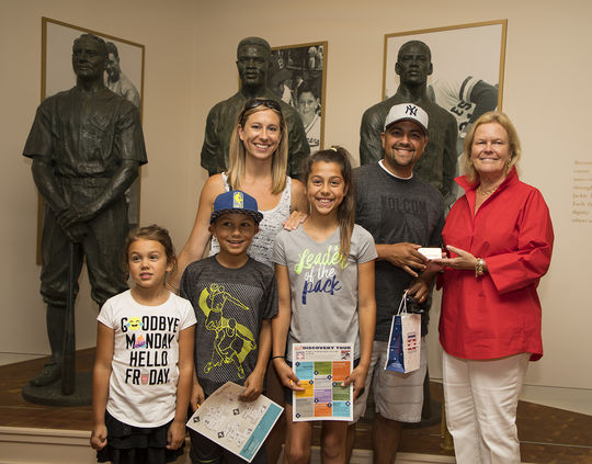 Sergio Armas, the seventeeth million visitor to the Hall of Fame, poses for a photo with his family and Hall of Fame Chairman of the Board, Jane Forbes Clark. (Milo Stewart Jr./National Baseball Hall of Fame and Museum)