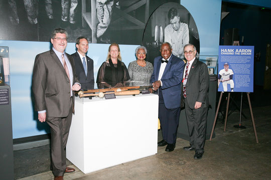 """Hank and Billye Aaron (second and third from right) pose with various artifacts from the Hall of Famer's career, at """"A Salute to the Life and Times of Henry Aaron."""" From left to right: Hall of Fame Vice President of Exhibitions and Collections Erik Strohl, Hall of Fame President Jeff Idelson, Hall of Fame Chairman of the Board Jane Forbes Clark, Billye Aaron, Hank Aaron and Allan Tanenbaum. (Images by Caselove Productions)"""