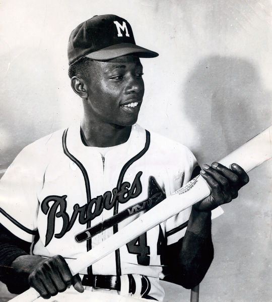 Two-time NL batting champion Henry Aaron sitting in chair posed with bat. BL-1431-92 (National Baseball Hall of Fame Library)
