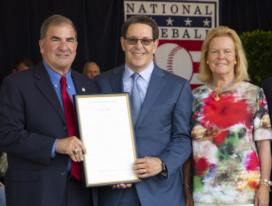 Hall of Fame President Tim Mead, left, and Chairman of the Board Jane Forbes Clark, right, present the 2019 J.G. Taylor Spink Award to Jayson Stark at the <em>Awards Presentation</em>. (Milo Stewart Jr./National Baseball Hall of Fame and Museum)