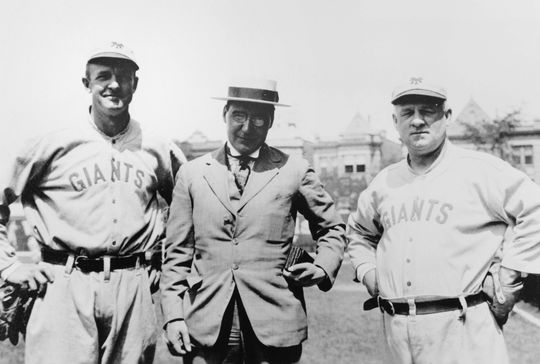 In this undated, cropped photograph, Mathewson stands on the left and his long-time manager John McGraw on the right.  The person in the center is unidentified.  BA-PF-Christy-Mathewson-Group-018  (National Baseball Hall of Fame and Museum)