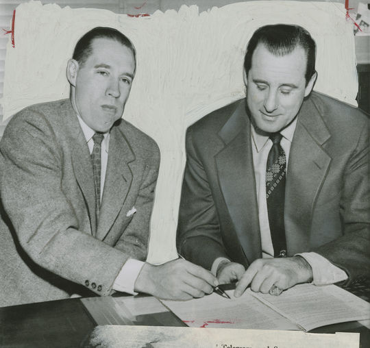 """Bob Feller, who spent his entire big league career with the Indians, is shown seated with Indians general manager Hank Greenberg. Greenberg indicates with his finger where Feller should sign his 17th contract with the Indians.  <a href=""""https://collection.baseballhall.org/islandora/object/islandora%3A612154"""">PASTIME</a> (National Baseball Hall of Fame and Museum)"""